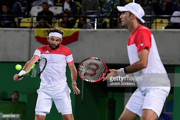Romania's Florin Mergea and Romania's Horia Tecau return the ball to Spain's Rafael Nadal and Spain's Marc Lopez during their men's doubles final...