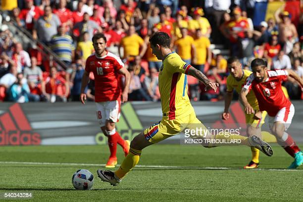 Romania's forward Bogdan Stancu scores a penalty during the Euro 2016 group A football match between Romania and Switzerland at the Parc des Princes...