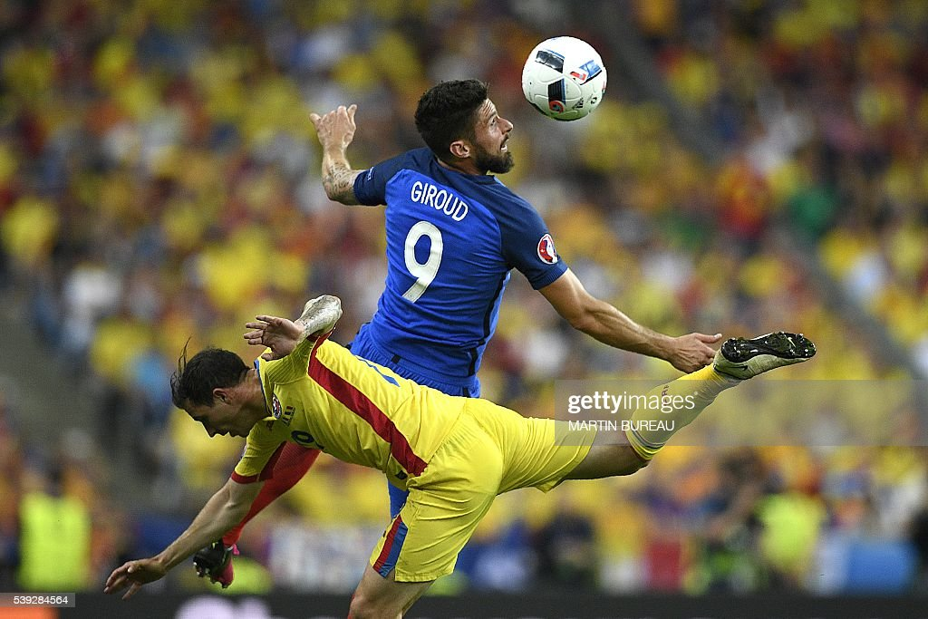 TOPSHOT - Romania's forward Bogdan Stancu (bottom) vies for the ball with France's forward Olivier Giroud during the Euro 2016 group A football match between France and Romania at Stade de France, in Saint-Denis, north of Paris, on June 10, 2016. France beat Romania 2-1 in the opening match of the Euro 2016. / AFP / MARTIN