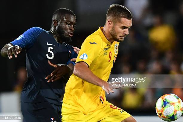 Romania's forward George Puscas outruns France's defender Dayot Upamecano during the Group C match of the U21 European Football Championships between...