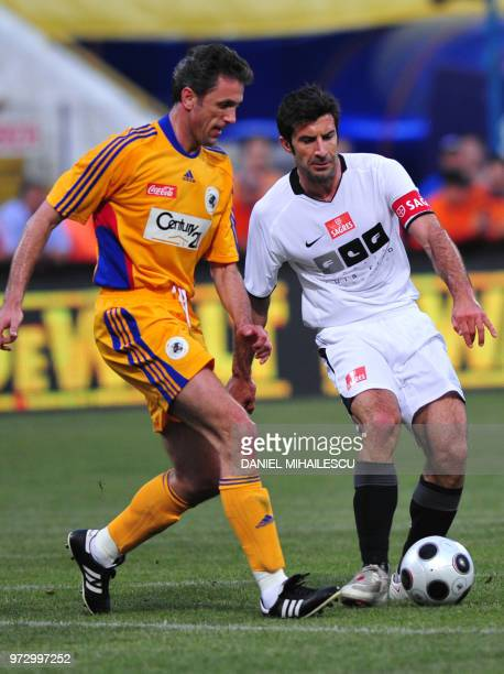 Romania's Gica Popescu vies for the ball with World Stars team's Luis Figo during the charity match 'The evening of the Champions' in Bucharest on...