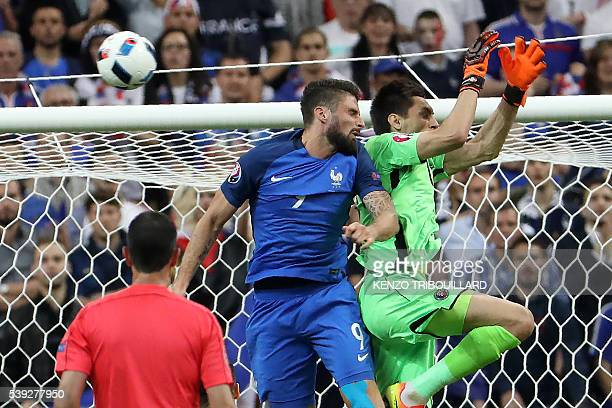 Romania's goalkeeper Ciprian Anton Tatarusanu jumps to miss the ball against France's forward Olivier Giroud during the Euro 2016 group A football...