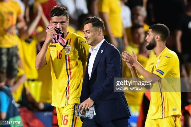Romania's head coach Matei Mirel Radoi talks with Romania's midfielder Dragos Nedelcu at the end of the Group C match of the U21 European Football...