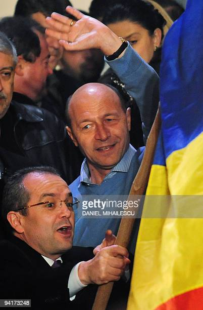 Romania's incumbent President Traian Basescu salutes supporters next to Prime Minister Emil Boc at DemocraticLiberal Party's headquarters on December...