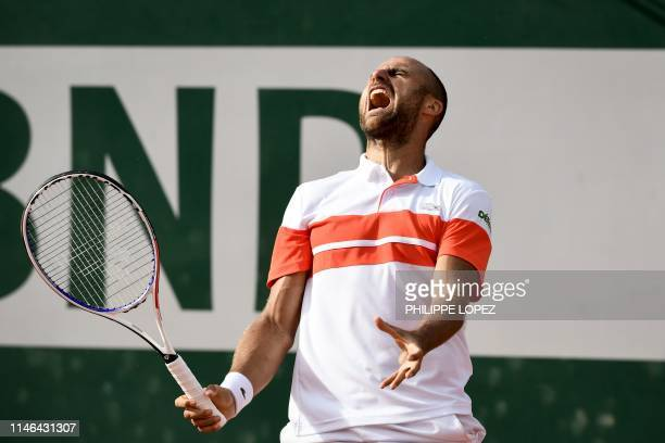 Romania's Marius Copil reacts as he plays against France's Benoit Paire during their men's singles first round match on day two of The Roland Garros...