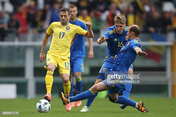 Romania's midfielder Lucian Sanmartean fights for the ball with Ukraine's forward Roman Zozulya and Ukraine's midfielder Serhiy Sydorchuk during the...