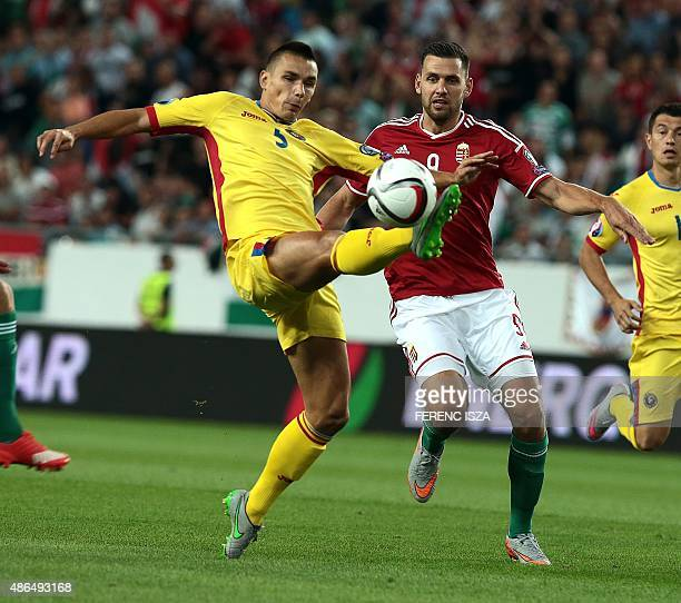 Romania's Ovidiu Hoban vies for the ball with Hungary's Adam Szalai during the Euro 2016 qualifying football match between Hungary and Romania in...