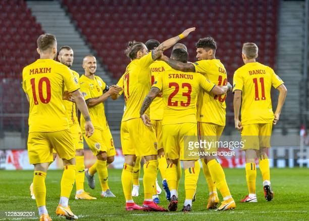 Romania's players celebrate scoring the opening goal during the UEFA Nations League football match between Austria and Romania on September 7, 2020...