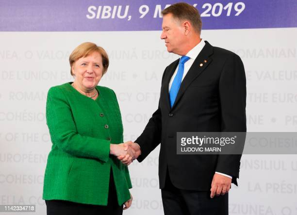 Romania's President Klaus Iohannis greets German Chancellor Angela Merkel arriving for a EU summit in Sibiu central Romania on May 9 2019 European...