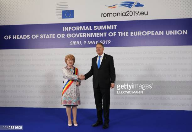 Romania's President Klaus Iohannis greets Sibiu's mayor Astrid Fodor on her arrival for a EU summit in Sibiu central Romania on May 9 2019 European...