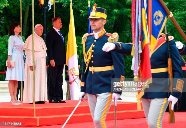 Romania's President Klaus Iohannis his wife Carmen Iohannis and Pope Francis inspect an honor guard at the Presidential Palace in Bucharest on May 31...