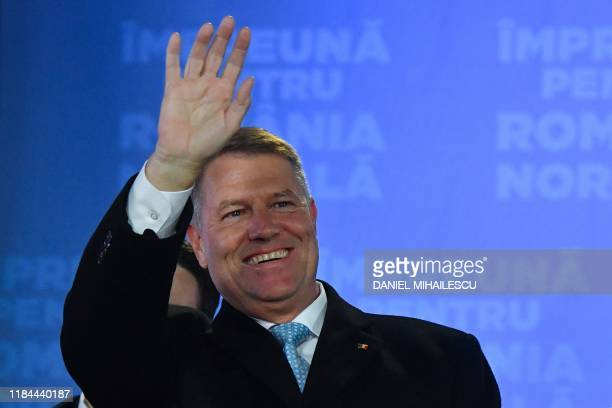 Romania's President Klaus Iohannis waves as he addresses the media at the ruling National Liberal Party headquarters, in Bucharest on November 24,...