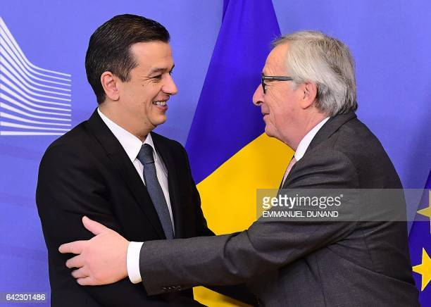 Romania's Prime Minister Sorin Grindeanu shakes hands with European Commission President JeanClaude Juncker upon his arrival at the European...