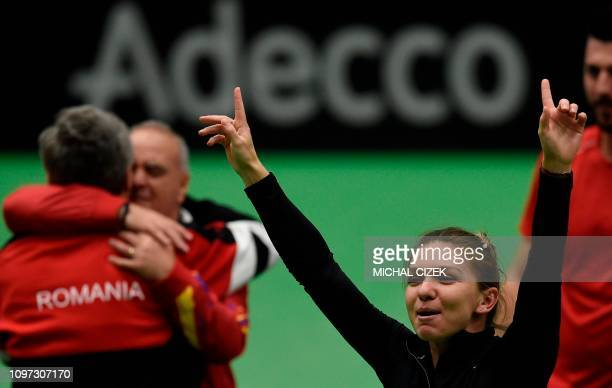 Romania's Simana Halep celebrates with members of Romanian Fed Cup team after they defeated the Czech Republic in Fed Cup tennis match between Czech...