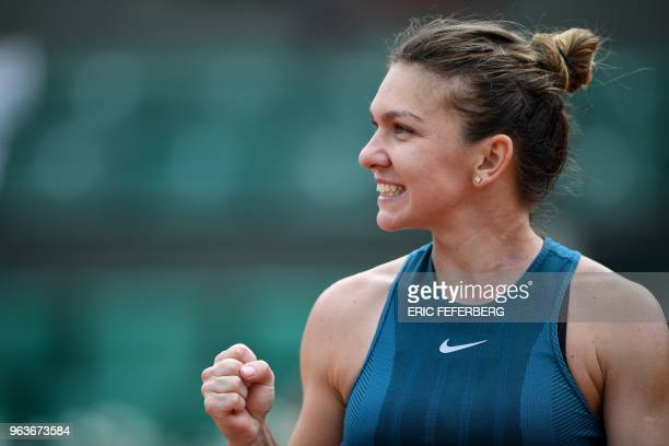 Romania's Simona Halep celebrates after victory at the end of her women's singles first round match against Alison Riske of the US on day four of The...