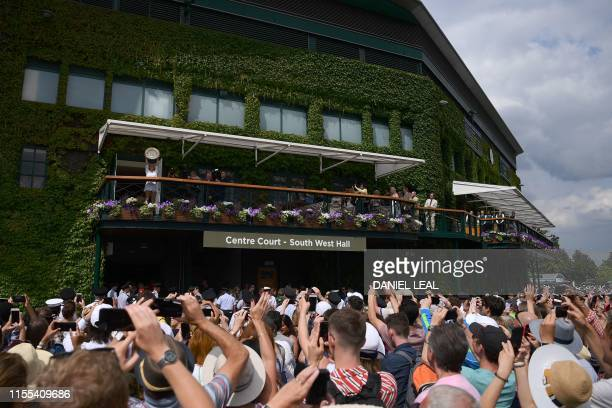 Romania's Simona Halep holds the winner's trophy up to the fans as she stands on the club house balcony after winning the women's singles final on...