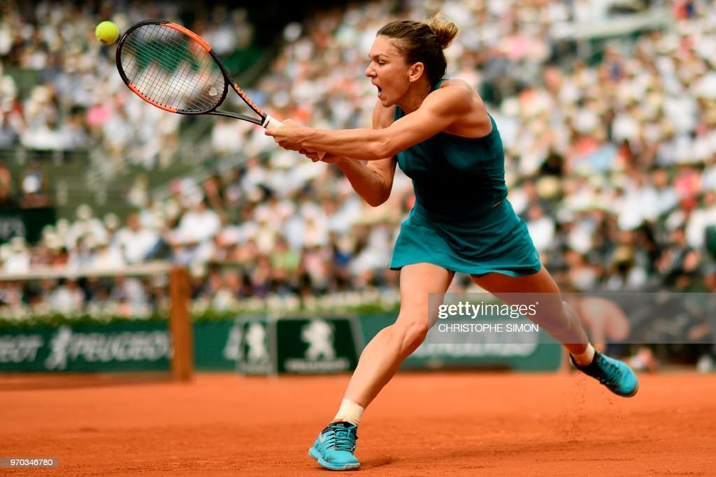 TOPSHOT - Romania's Simona Halep plays a backhand return to Sloane Stephens of the US during their women's singles final match on day fourteen of The Roland Garros 2018 French Open tennis tournament in Paris on June 9, 2018.
