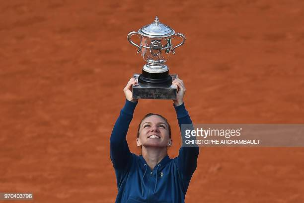 TOPSHOT Romania's Simona Halep poses with her trophy after winning the women's singles final match against Sloane Stephens of the US on day fourteen...