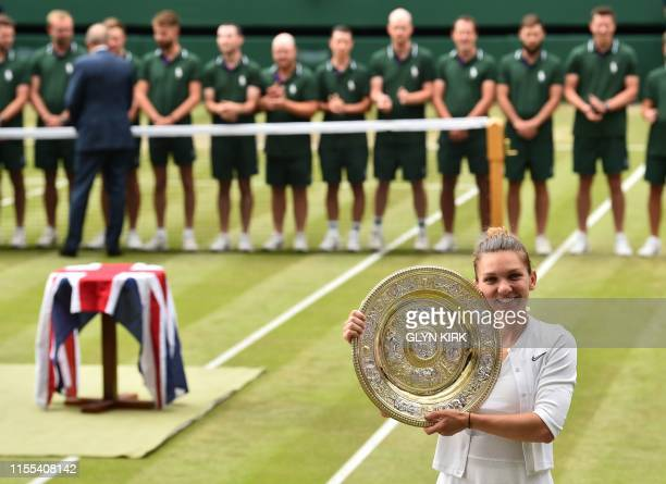 Romania's Simona Halep poses with the Venus Rosewater Dish trophy after beating US player Serena Williams during their women's singles final on day...