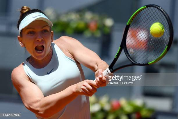 Romania's Simona Halep returns the ball to Australia's Ashleigh Barty during their WTA Madrid Open round of 8 tennis match at the Caja Magica in...