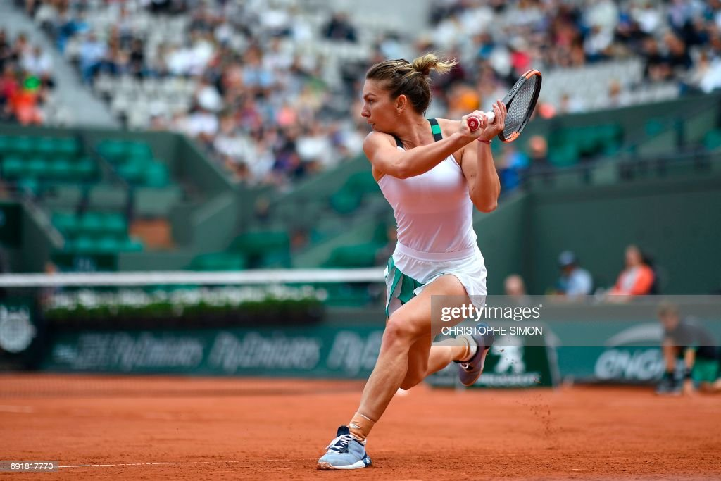 TOPSHOT - Romania's Simona Halep returns the ball to Russia's Darya Kasatkina during their tennis match at the Roland Garros 2017 French Open on June 3, 2017 in Paris. /
