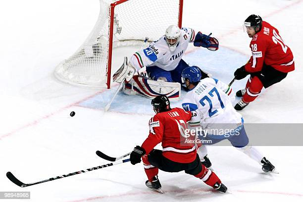 Romano Lemm of Switzerland is challenged by Michael Souza and goalkeeper Daniel Bellissimo of Italy during the IIHF World Championship group B match...