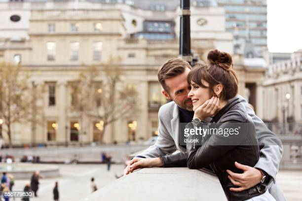 romantic adult couple embracing at trafalgar square, autumn season - a fall from grace stock pictures, royalty-free photos & images