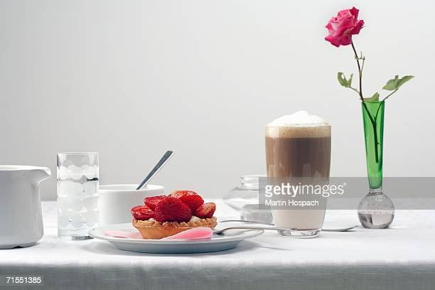 Romantic breakfast with strawberry tart and rose