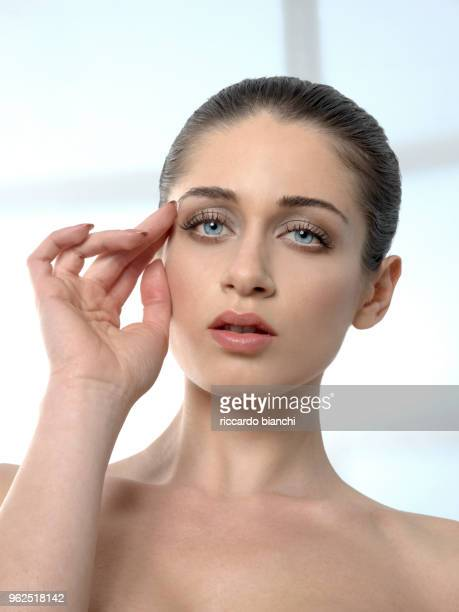romantic brunette woman with hand on face and blue eyes
