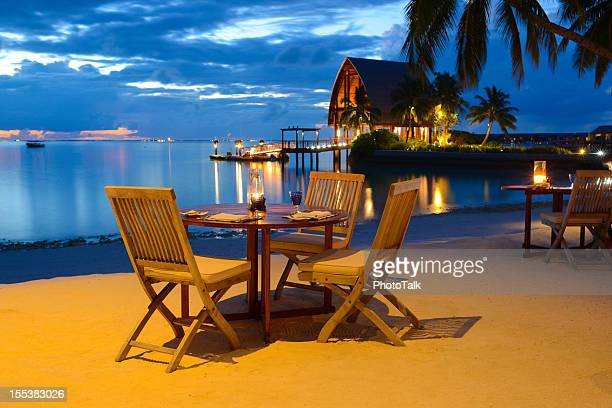 romantica cena a lume di candela sulla spiaggia al ristorante sul mare - riva dell'acqua foto e immagini stock