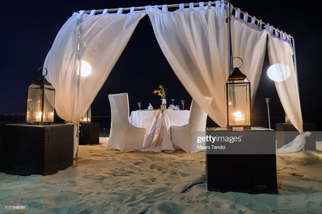 Romantic candlelit table facing the ocean on the beaches of Nusa Dua. : Foto stock
