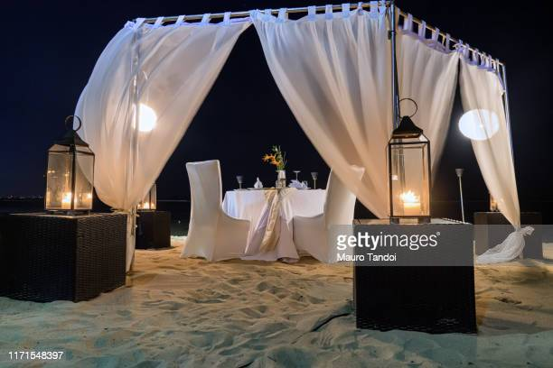 romantic candlelit table facing the ocean on the beaches of nusa dua. - mauro tandoi stock photos and pictures