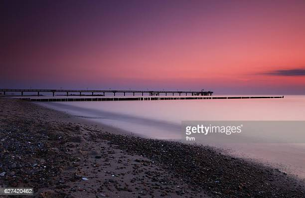 romantic colorful sunset on the beach at baltic sea (fischland/ germany) - sunset beach stock photos and pictures