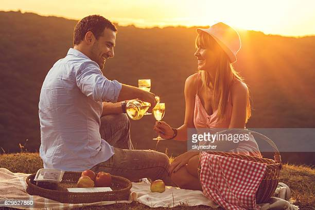 Romantic couple at sunset enjoying with glass of wine.