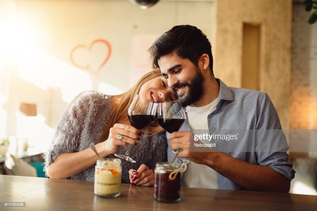 Romantic couple cheers with red wine and celebrating Valentine's day. : Stock Photo