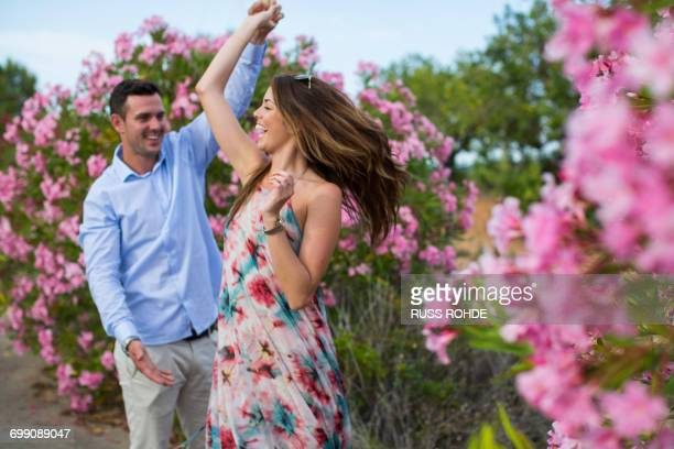 Romantic couple dancing and swirling by blossoms, Majorca, Spain