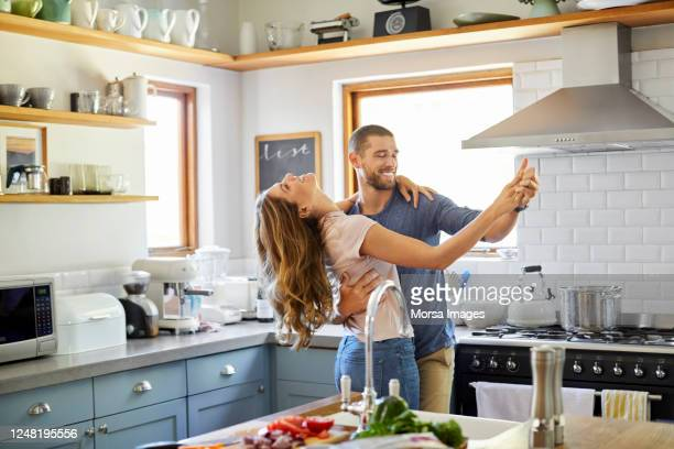 romantic couple dancing in kitchen at home - heterosexual couple stock pictures, royalty-free photos & images