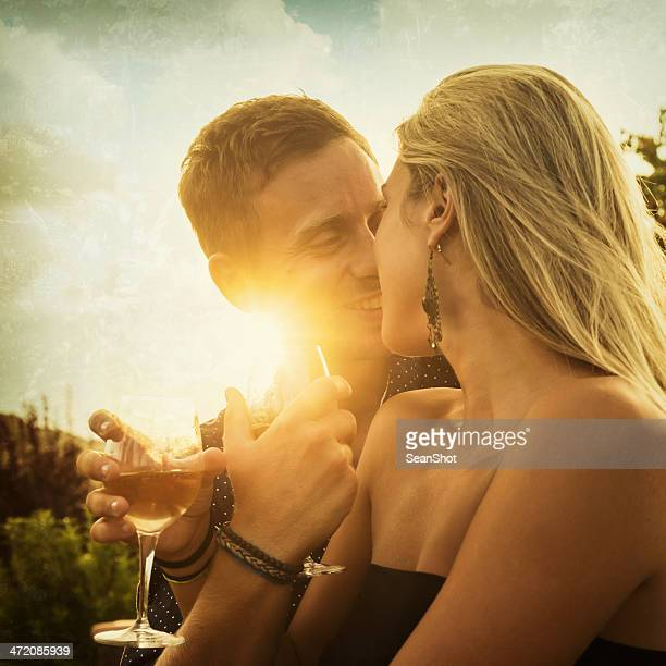 Romantic couple drink wine and gaze into eyes at sunset