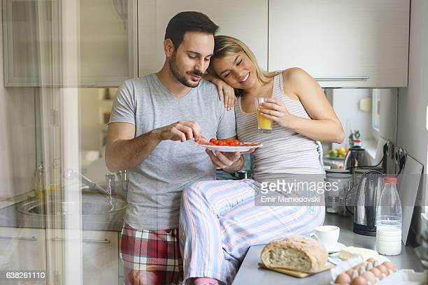 Romantic couple enjoying breakfast and romance on weekend morning.