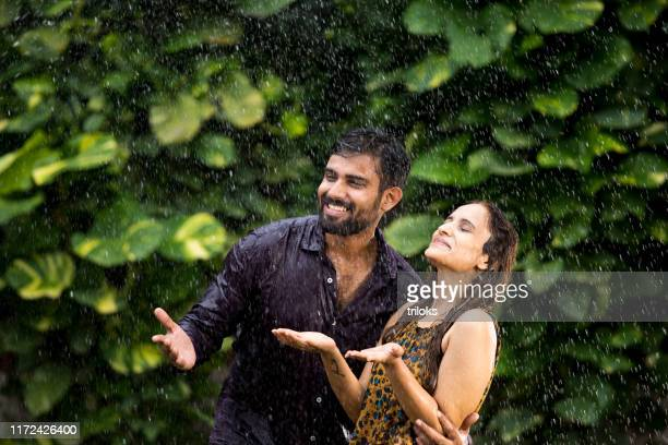 romantic couple enjoying the rain - husband stock pictures, royalty-free photos & images