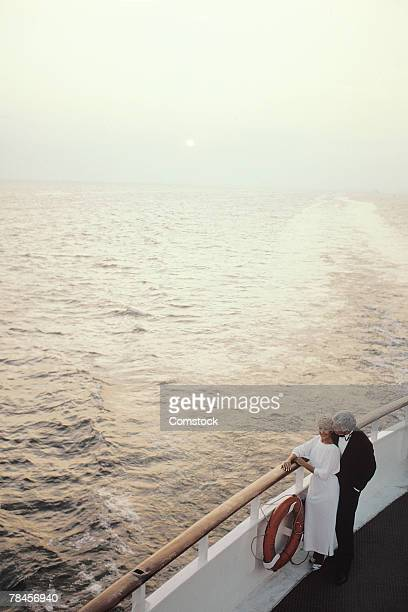 Romantic couple enjoying view from deck of cruise ship