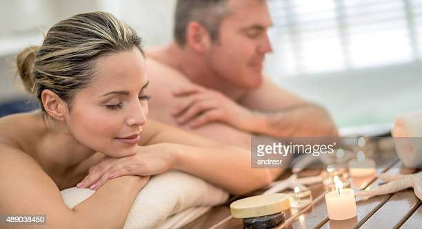 romantic couple getting pampered at the spa - massage couple photos et images de collection
