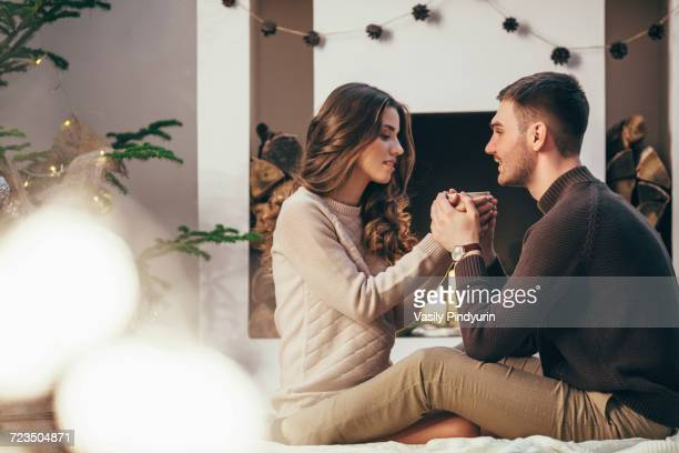 Romantic couple having coffee while sitting at home during Christmas