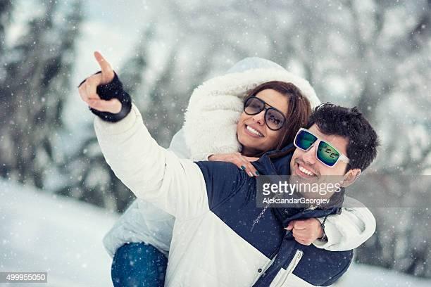Romantisches Paar, die Spaß mit Huckepack nehmen Sie auf dem Schnee
