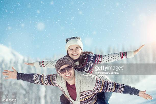 Romantic Couple Having Fun with Piggyback Ride on the Snow