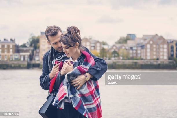 Romantic couple hugging on the riverbank in the city