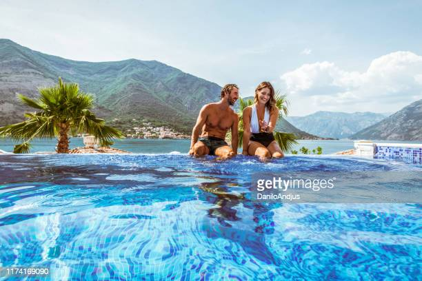 romantic couple in a pool - close to stock pictures, royalty-free photos & images