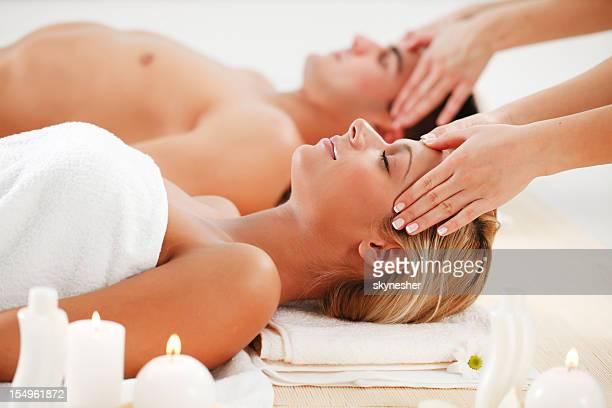 Pareja romántica está teniendo un masaje de cabeza en el centro de spa.
