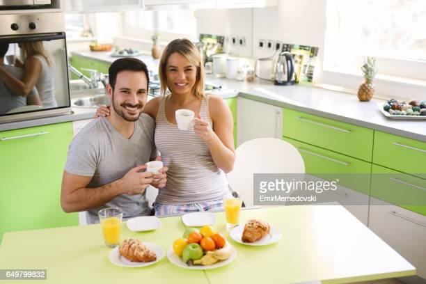 Romantisch zu zweit sitzt in der Küche genießen Frühstück und Romantik auf Wochenende Morgen.