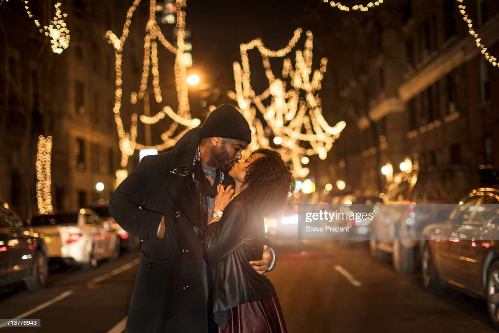 Romantic couple kissing by Christmas lights at night, New York, USA : Stock Photo